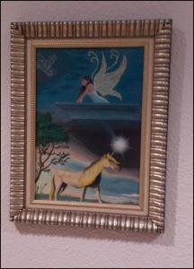 Se encuentra el cuadro de la pintura con su marco colgado en la pared. En la pintura aparecen Se muestra un unicornio y un hada como personajes principales, en dos mundos separados por una perspectiva cónica focal sobre un punto blanco con destellos.