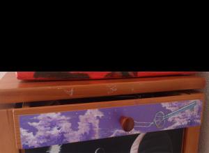Fotografía del cajón al que se le pinta un fondo en tonos violeta con nubes y una llave de tipo histórico.