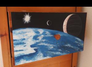 Fotografía del cajón al que se le pinta un punto de un sistema planetario ficticio, con un planeta oceánico en primer plano y un planeta similar a Júpiter con bastante cercanía.