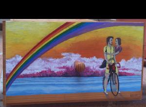 Fotografía del cajón al que se le pinta una pareja de enamorados, él de pie junto a su bicicleta y ella sentada en el sillín y sujetada por él. A los dos los envuelve un arcoiris y de fondo un mar con nubes de tormenta al fondo.