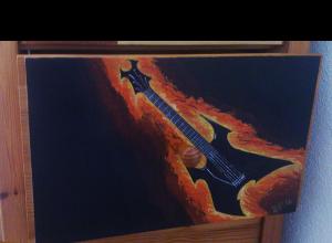 Fotografía del cajón al que se le pinta una guitarra eléctrica con estética de música metal en color negro, envuelta en llamas y sobre fondo negro.