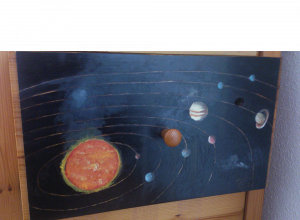 Fotografía del cajón al que se le pinta el sistema solar desde un punto de vista elevado y saliendo humo del Sol como elemento ficticio.