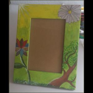 Fotografía del portaretratos de cartón impreso, pintado con fondo en color degradado verde hacia amarillo, con tres elementos: un árbol en perspectiva, una flor color violeta blanqueado y una flor de loto.