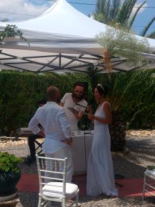 Aparecen los novios, vestidos de blanco, junto al reverendo vestido de blanco detrás de la mesa de ceremonias y bajo una pérgola con tela blanca.