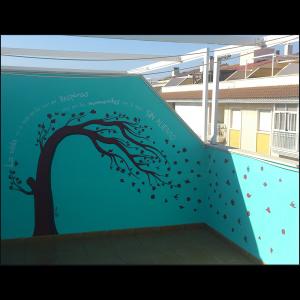 Mural con fondo verde azulado con un árbol bicolor en marrón oscuro y negro, torcido a la derecha por el viento. Sus hojas, con diferentes formas geométricas, se esparcen por toda la superficie de la pared simulando el efecto del otoño.