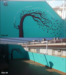 En ambas fotos, el mural completamente terminado. Arriba, fotografía que enfoca al árbol torcido por la acción del viento, con sus hojas esparcidas por los muros. Debajo, fotografía de un punto de vista alejado donde se puede ver todo el conjunto.