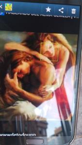 Fotografía tomada desde un smartphone enfocando a la pantalla de otro teléfono móvil. En dicha pantalla aparece imagen de lo que parece ser una pintura artística. En primer plano están dos personajes, un hombre y una mujer sentados en el suelo.