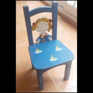 Silla hecha exclusivamente en madera, incluido el asiento. El asiento tiene pintados sobre la capa base de pintura, tres barquitos veleros. En el respaldo hay una silueta humana de pecho para arriba. La silueta está pintada con la caricatura simple de una niña marinera rubia. Viste una camisa azul con una ancla en el pecho y un collar en el cuello.